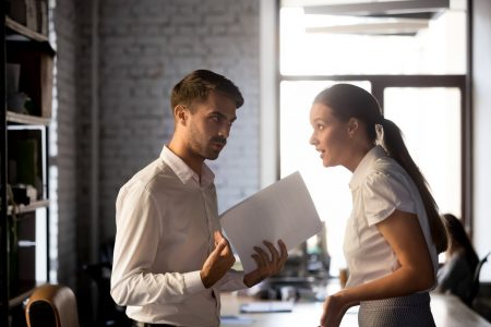 Millennial diverse employees standing holding financial paperwork, disputing over statistics or contract terms, man and woman have misunderstanding in office, argue or quarrel on document or report